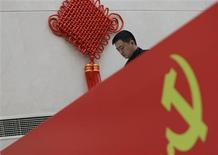 A man walks past a logo of the Communist Party of China (CPC) at a media center for the upcoming18th National Congress of the CPC, which starts Thursday, in Beijing November 5, 2012. REUTERS/Jason Lee