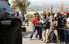 Striking miners react as they make way for a security vehicle at the AngloGold Ashanti mine in Carletonville, northwest of Johannesburg October 25, 2012. REUTERS/Siphiwe Sibeko