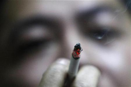 A man smokes at an office in Shanghai March 3, 2009. REUTERS/Aly Song/Files