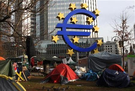 Tents of the 'Occupy Frankfurt' movement are pictured next to the Euro currency sign sculpture in front of the European Central Bank (ECB) headquarters during a protest in Frankfurt December 8, 2011. REUTERS/Alex Domanski