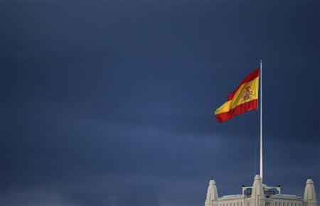A Spanish flag flutters in the wind on the top of Madrid's city hall as rain clouds appear in the background September 26, 2012. REUTERS/Sergio Perez