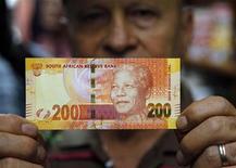 Sudáfrica ha inmortalizado al ex presidente Nelson Mandela el martes en una serie de nuevos billetes que llevan la imagen del líder anti-apartheid, que sigue siendo una fuerza unificadora en un país todavía con cicatrices por su pasado de división racial. En la imagen, el dueño de una tienda muestra los nuevos billetes con la imagen de Mandela en Pretoria el 6 de noviembre de 2012. REUTERS/Siphiwe Sibeko