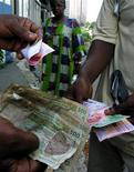 People exchange money in Abidjan, December 31, 2004. REUTERS/Thierry Gouegnon