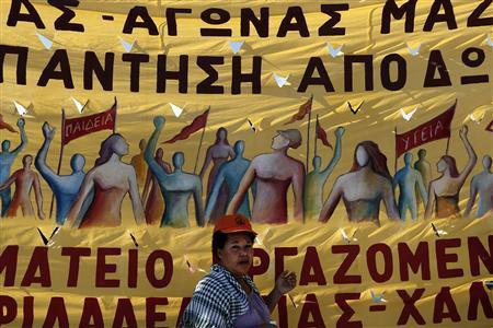 A protester stands in front of a banner during an anti-austerity rally in front of the parliament in Athens November 6, 2012. REUTERS/Yorgos Karahalis