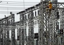 An employee works on electric pylons at a power station in Greater Noida on the outskirts of New Delhi June 8, 2012. REUTERS/Parivartan Sharma