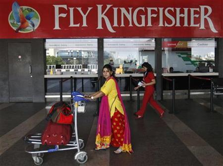 A passenger walks with her luggage in front of a Kingfisher Airlines reservation office at the domestic airport in Mumbai October 23, 2012. REUTERS/Danish Siddiqui