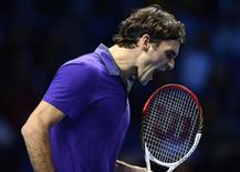 Roger Federer logró un nuevo récord al ganar a Janko Tipsarevic en primera ronda de las finales del World Tour el martes, situándose en lo más alto de la lista de jugadores con más victorias en torneo que cierra la temporada de la ATP. En la imagen, el tenista suizo Roger Federer celebra un punto ganador contra el serbio Janko Tipsarevic durante su partido de indiviuales de las finales del World Tour de la ATP en el O2 Arena de Londres, el 6 de noviembre de 2012. REUTERS/Dylan Martinez