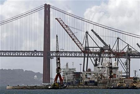 Cranes and ships are seen at the Lisbon harbour with the Tagus river bridge in the background October 25, 2012. Portuguese dock workers have been striking on and off since September 17. REUTERS/Jose Manuel Ribeiro