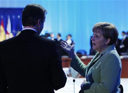 German Chancellor Angela Merkel (R) talks with Britain's Prime Minister David Cameron before the first session of the G20 Summit in Los Cabos June 18, 2012. REUTERS/Edgard Garrido