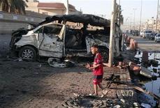 Un bambini davanti ai resti di un'autobomba esplosa a Sadr City, un quartiere di Baghdad, 28 ottobre 2012. REUTERS/Wissm al-Okili
