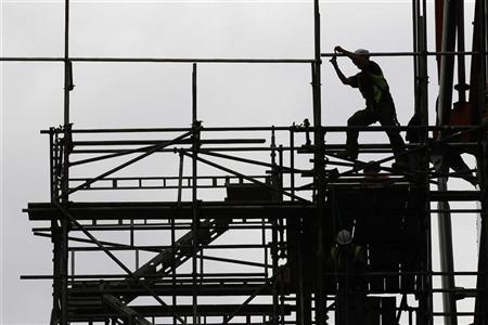 A man works on scaffolds at a construction site in central London July 23, 2010. REUTERS/Stefan Wermuth