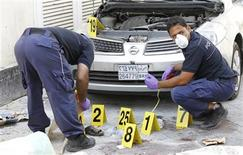 Police officials work at a bomb site in capital of Manama, Bahrain, November 5, 2012. Five bombs exploded in the heart of the Bahraini capital Manama on Monday, killing two people, officials said, in rare attacks targeting civilians during the 21-month-old uprising against the kingdom's U.S.-backed rulers. REUTERS/Hamad I Mohammed