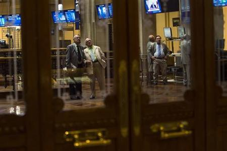 Traders look at electronic boards at the Madrid stock exchange June 26, 2012. REUTERS/Susana Vera/Files