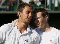 Frederik Nielsen of Denmark (L) and Jonathan Marray of Britain embrace after defeating Bob Bryan of the U.S. and Mike Bryan of the U.S. in their men's semi-final doubles tennis match at the Wimbledon tennis championships in London July 6, 2012. REUTERS/Stefan Wermuth