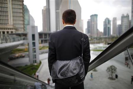 A business man rides an escalator in the financial district of Pudong in Shanghai September 21, 2011. REUTERS/Aly Song/Files