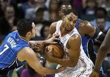 Charlotte Bobcats guard Gerald Henderson (C) fights for control of the ball against Orlando Magic shooting guard J.J. Redick (L) in their NBA basketball game in Charlotte, North Carolina December 30, 2011. REUTERS/Chris Keane