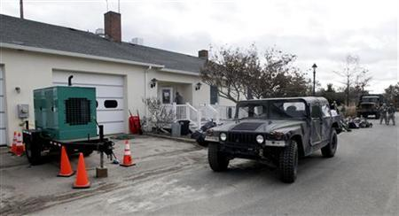 An electrical generator and military vehicle are parked outside the Bay Head Fire Company providing power so that people can vote in the aftermath of Hurricane Sandy, during the U.S. presidential elections in Bay Head, New Jersey, November 6, 2012. REUTERS/Tom Mihalek