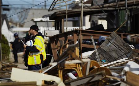 A gas company employee pauses while he surveys damage incurred by hurricane Sandy in the Queens borough region of Breezy Point in New York, November 6, 2012. REUTERS/Lucas Jackson