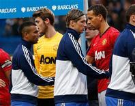 El lateral izquierdo inglés Ashley Cole se perderá el partido del actual ganador de Liga de Campeones, el Chelsea, contra el Shakhtar Donetsk el miércoles en el grupo B de la competición por una lesión en los isquiotibiales. En la imagen, el jugador del Manchester united Rio Ferdinand (a la derecha) estrecha la mano del jugador del Chelsea Ashley Cole (a la izquierda) en su partido de Premier League en Stamford Bridge en Londres, el 28 de octubre de 2012. REUTERS/Eddie Keogh