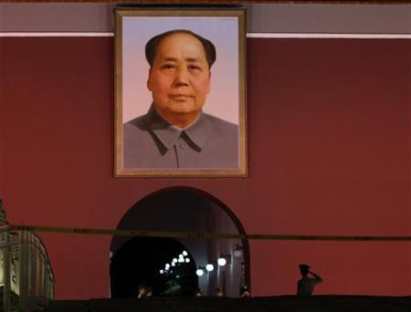 A paramilitary police officer salutes as he poses for a photo in front of a giant portrait of China's late Chairman Mao Zedong at Beijing's Tiananmen Gate, September 28, 2012. REUTERS/Jason Lee/Files