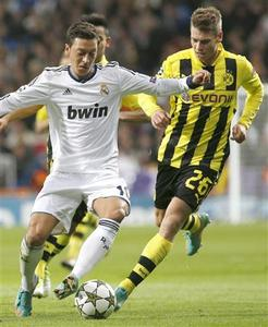 Real Madrid's Mesut Ozil (L) controls the ball against Borussia Dortmund's Lukasz Piszczek during their Champions League Group D soccer match at Santiago Bernabeu stadium in Madrid, November 6, 2012. REUTERS/Juan Medina