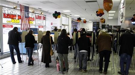 Voters line-up to cast their votes at Mid-City Nissan car dealer as Abbey Garcia crawls around the floor during the U.S. presidential election in Chicago, Illinois, November 6, 2012. REUTERS/Jeff Haynes