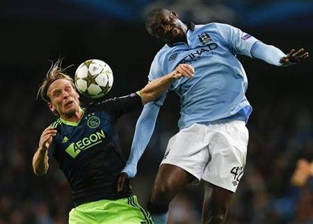 Manchester City's Yaya Toure (R) challenges Ajax Amsterdam's Christian Poulson during their Champions League Group D soccer match at The Etihad Stadium in Manchester, northern England, November 6, 2012. REUTERS/Phil Noble (BRITAIN - Tags: SPORT SOCCER)