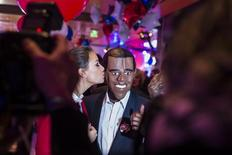 A woman kisses a man wearing a mask of U.S. President Barack Obama during the U.S. election night at the representation of the Bertelsmann media cooperation in Berlin November 6, 2012. REUTERS/Thomas Peter