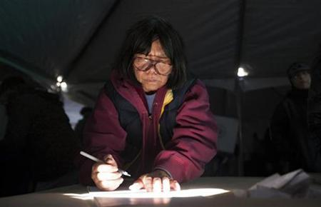 A woman uses a shaft of sunlight to see her ballot as she votes in a polling site built to service residents of the Queens borough neighborhoods of Breezy Point and the Rockaways, whose original site was damaged during Hurricane Sandy, during the U.S. presidential election in New York, November 6, 2012. REUTERS/Lucas Jackson