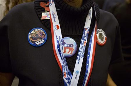 A woman displays badges in support of the Democratic candidate, U.S. President Barack Obama during an election party, during the U.S. Presidential election, at the U.S. Embassy in London, November 6, 2012. REUTERS/Neil Hall)