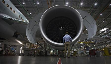 A worker stands in front of an engine on the Boeing 777 at their assembly operations in Everett, Washington, October 18, 2012. REUTERS/Andy Clark