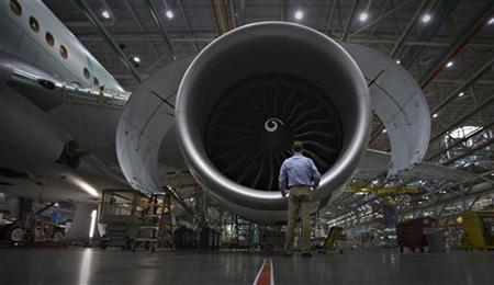 A worker stands in front of an engine on the Boeing 777 at their assembly operations in Everett, Washington, October 18, 2012. REUTERS/Andy Clark/Files