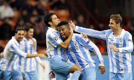 Malaga's Eliseu (2nd R) celebrates with his team mates Javier Saviola (L) and Joaquin after scoring against AC Milan during their Champions League Group C soccer match at San Siro stadium in Milan November 6, 2012. REUTERS/Alessandro Garofalo