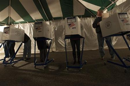 Voters cast their vote at ballot booths, under lights powered by generators, during the U.S. presidential election in the Staten Island Borough of New York November 6, 2012. REUTERS/Keith Bedford