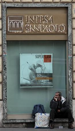 A man sits in front of Intesa Sanpaolo bank in downtown Rome December 8, 2011. REUTERS/Alessandro Bianchi