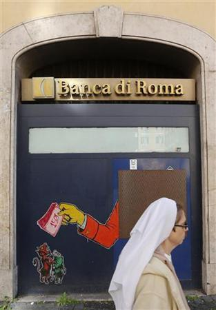 A nun walks past an automated teller machine, which has been boarded up, as a graffiti depicting an arm feeding money to a devil, wolf and pig is seen in downtown Rome November 2, 2012. REUTERS/Alessandro Bianchi