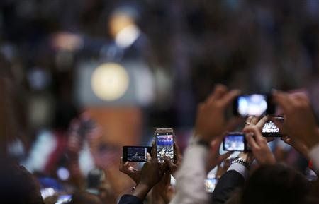 People take pictures as U.S. President Barack Obama speaks after winning the U.S. presidential election, in Chicago, Illinois, REUTERS/John Gress