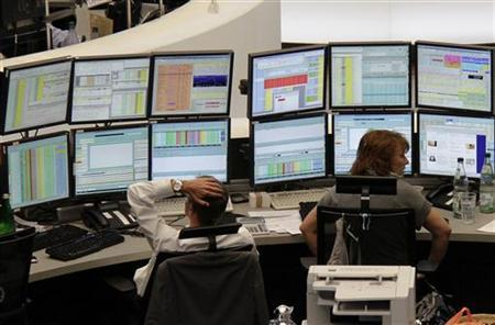 Traders work at their desks at Frankfurt's stock exchange August 11, 2011. REUTERS/Remote/Pawel Kopczynski/Files