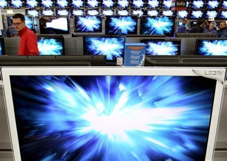 A customer walks past TV screens at a newly opened store of German electronics retailer Saturn in the town of Volketswil near Zurich April 22, 2010. REUTERS/Arnd Wiegmann