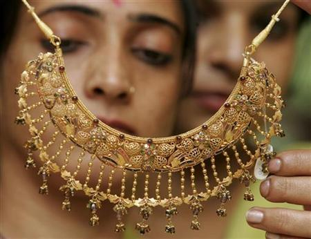 Women admire a gold necklace at a jewellery shop in Chandigarh October 18, 2007. REUTERS/Ajay Verma/Files