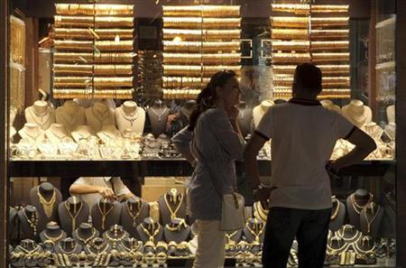 A Turkish couple look into jewellery shop where gold bangles are on display in Grand Bazaar in Istanbul June 29, 2012. REUTERS/Murad Sezer/Files
