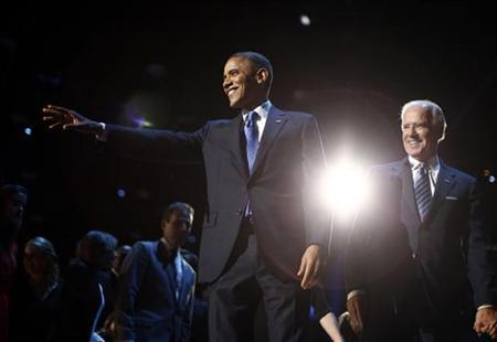 U.S. President Barack Obama (L) points to the crowd during his election night victory rally in Chicago, November 7, 2012, alongside Vice President Joe Biden. REUTERS/Jason Reed