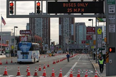 A bus enters Holland Tunnel while police officers stand guard at its entrance at Jersey City in New Jersey November 2, 2012. REUTERS/Eduardo Munoz