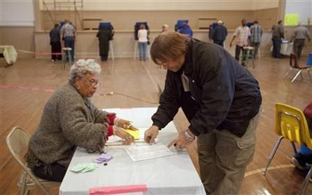 Poll worker Catherine Smith (L) checks in voter Daniel Gaines Jr., after he showed his ID at the Cottageville Municipal Complex during the U.S. presidential election in Cottageville, South Carolina, November 6, 2012. REUTERS/Randall Hill