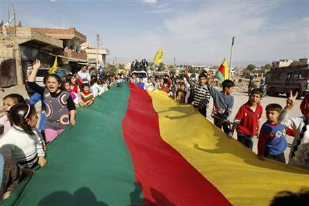Syrian Kurd children hold a giant flag during a protest in Derik, Hasakah November 1, 2012. REUTERS/Thaier al-Sudani
