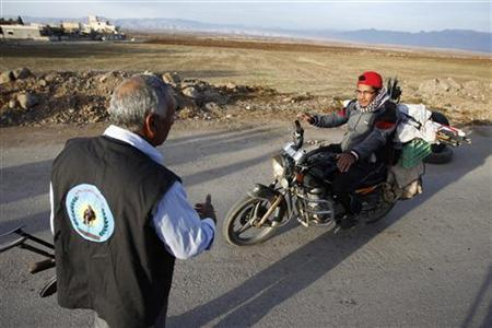 A Syrian Kurd Asaish officer speaks to a motorcyclist at a security checkpoint at Derik, in Al-Hasakah October 31, 2012. REUTERS/Thaier al-Sudani
