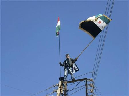 A protester on an power pole holds the Kurdish flag and the Syrian opposition flag (R) during a protest against Syria's President Bashar al-Assad, and celebrating Nowruz held by Kurdish community in Qamishli March 21, 2012. REUTERS/Handout/Files