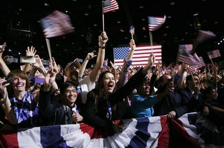 People wave flags and listen to President Barack Obama's victory speech in Chicago Novermber 7, 2012. REUTERS/Kevin Lamarque