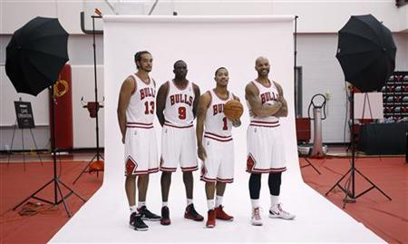 Chicago Bulls Joakim Noah (13) and teammates, Luol Deng (9), Derrick Rose (1) and Carlos Boozer (R) pose for photographs during media day for their upcoming NBA basketball season in Deerfield, Illinois, October 1, 2012. REUTERS/Jeff Haynes