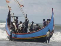 Members of Bangladesh Navy are seen with people rescued from a sunken boat in Bay of Bengal in Teknaf November 7, 2012. A boat carrying about 110 Bangladeshis and Rohingya Muslims from neighbouring Myanmar sank in the Bay of Bengal on Wednesday as they were heading to Malaysia and about half of them were missing, a Bangladeshi border force officer said. REUTERS/Stringer